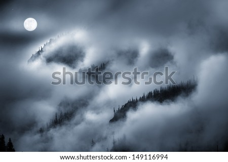 Photographic illustration of a night time Fog Covered Mountain lit by bright Full Moon. Makes for a spooky background for Halloween illustration or a moody nature theme. - stock photo