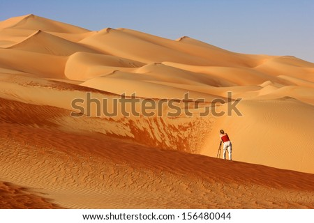 Photographing abstract patterns in the dunes of the Rub al Khali or Empty Quarter. Straddling Oman, Saudi Arabia, the UAE and Yemen, this is the largest sand desert in the world. - stock photo