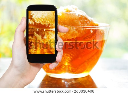 photographing food concept - tourist takes picture of fresh honey in comb in glass bowl at table on smartphone, Russia - stock photo