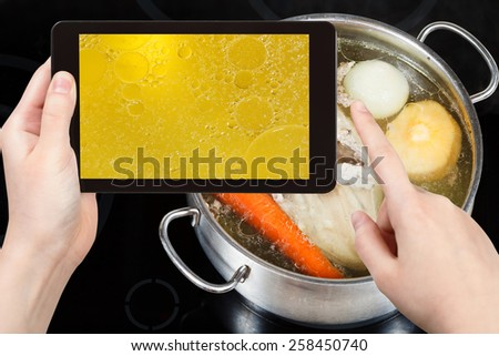 photographing food concept - tourist taking photo of boiling of chicken broth on mobile gadget - stock photo