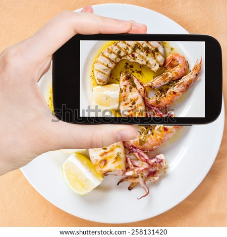 photographing food concept - tourist taking photo of sicilian grilled fish mix on white plate on mobile gadget, Sicily, Italy - stock photo