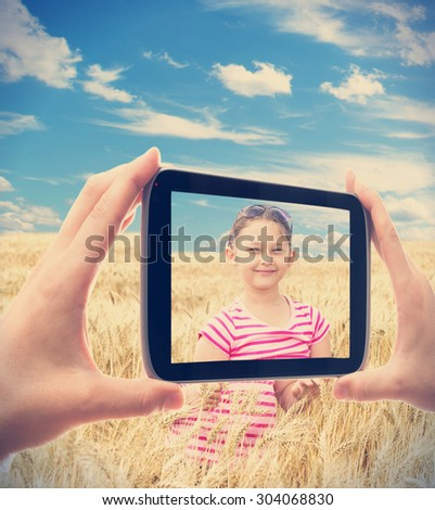 photographing smartphone girl in wheat - stock photo