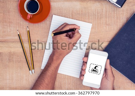 Photography apps against overhead view of businessman hand holding smart phone while writing - stock photo