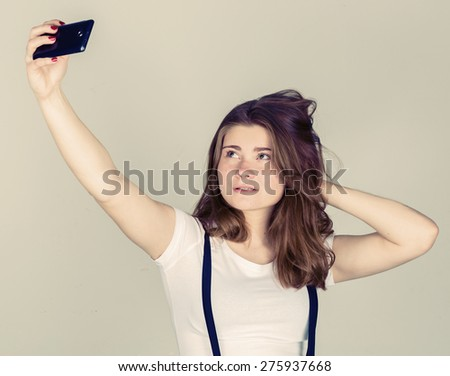 photography. Cheerful young  woman holding mobile phone and making photo of herself while standing against grey background - stock photo