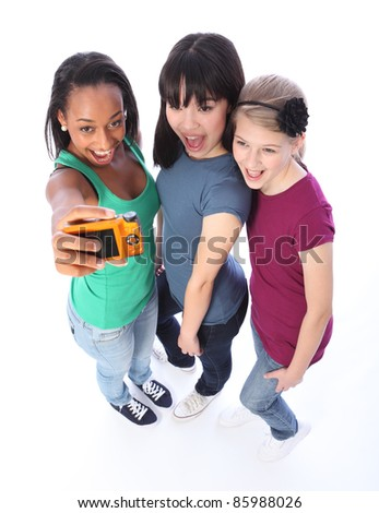 Photography fun with digital camera for three pretty young teenager girl friends a blonde caucasian, an oriental Japanese and an African American mixed race student all having a laugh together. - stock photo