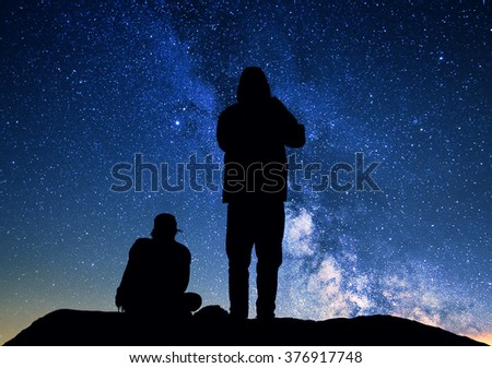 Photography of milky way and two people who look at the night sky full of stars and wait the dawn.  Black silhouettes on a dark background of the sky. - stock photo