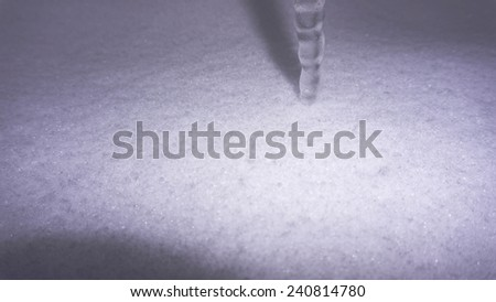 Photography of natural icicle on snow background. - stock photo