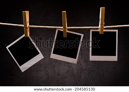 Photography paper with instant polaroid photo frames attached to rope with clothes pins. Copy space for your image. - stock photo