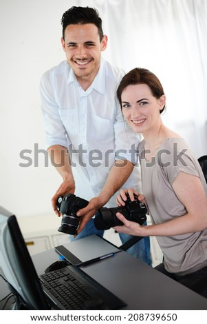 photography student and teacher viewing and editing photos with digital camera and computer - stock photo