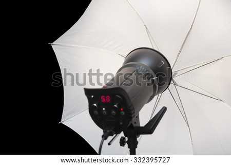 photography studio strobe flash with white umbrella and black copy space