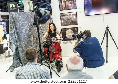 PHOTOKINA, COLOGNE - SEPTEMBER 19, 2014: people watch the demonstration of flashlight equipment at Photokina  - World of Imaging - in Cologne, Germany.