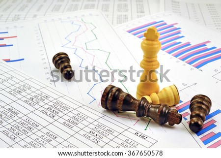 Photos chess pieces with graphs and numbers in the tables - stock photo