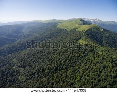 Photos from the bird's-eye view. The mountain ridge covered with forest. Mountain landscape. Caucasus.
