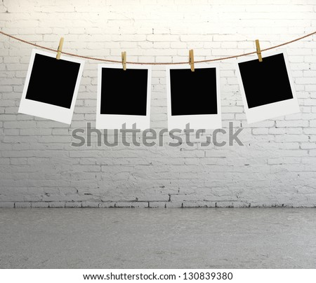 photos hanging on a rope in brick room - stock photo