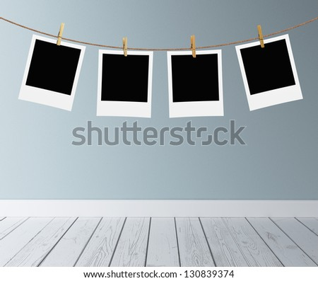 photos hanging on a rope in room - stock photo