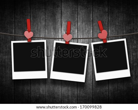 photos hanging on clothesline with heart clothespins over wooden background - stock photo