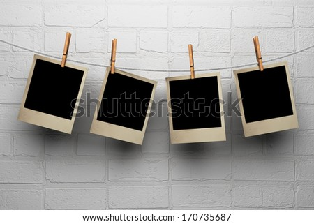 Photos hanging on clothespegs against a white wall