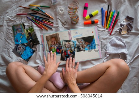 Photos in hands and photo album on grey blanket in the bed, Creating photo book for child with Down's syndrome