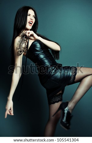 Photos of beautiful sexy girls in leather dress in the studio - stock photo