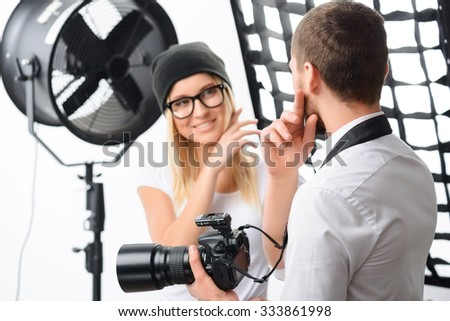 Photoshoot issues. Young male photographer talks with female model about important photoshoot issues - stock photo