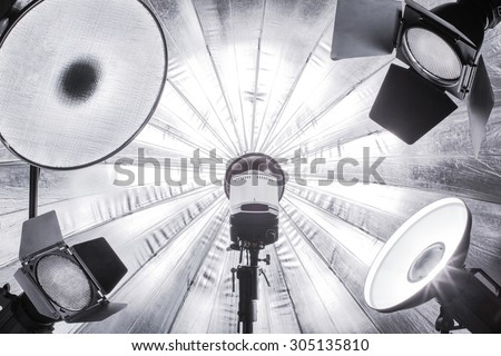 Photostudio lighting set up. Big silver umbrella on background and five flashes with reflectors and beauty dishes with grids in front. - stock photo