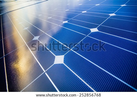 Photovoltaic cells and reflection of sunset light and clouds - stock photo