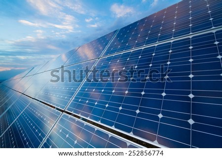 Photovoltaic cells with reflection of cloudy sky on sunset  - stock photo