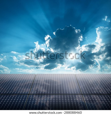 Photovoltaic ecological modules against of sun behind cloudy sky - stock photo