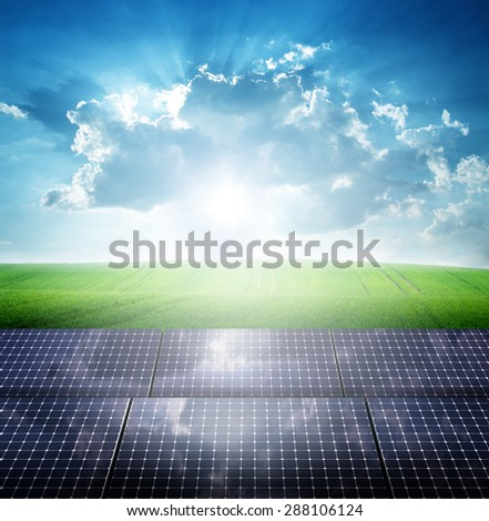 Photovoltaic ecological modules on green grass valley against of sun behind cloudy sky - stock photo