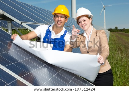 Photovoltaic engineer and contractor with construction plan at solar panels - stock photo