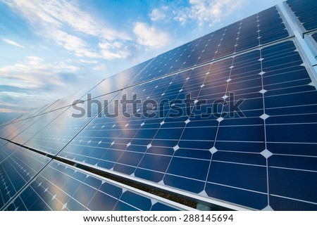 Photovoltaic modules reflect sunset light and clouds - stock photo