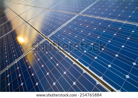 Photovoltaic modules rows and reflection of cloudy sky and setting sun - stock photo