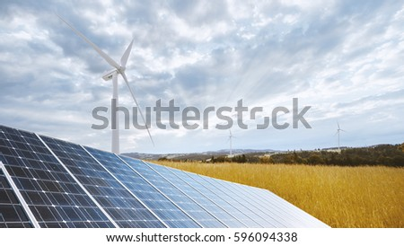 Photovoltaic panel and Wind mills against cloudy sky with sun beams - Ecological and renewable energy production