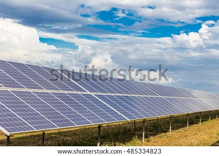 photovoltaic panels under cloudy bright blue sky
