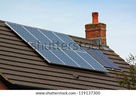Photovoltaic Solar and central heating panels on tiled roof of residential home - stock photo