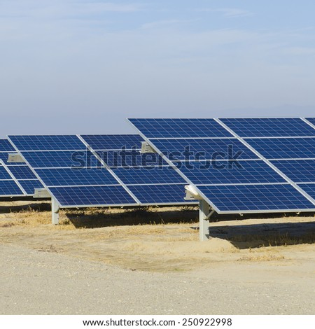 Photovoltaic solar collector panels set up in an ag area of southwest California - stock photo
