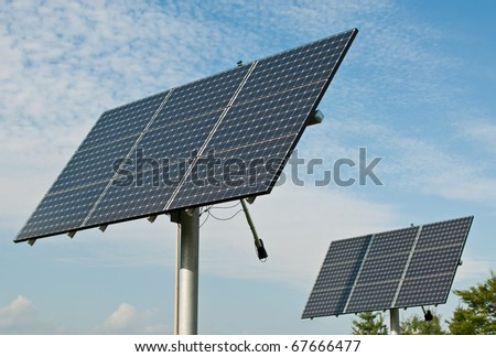 Photovoltaic solar panel arrays with blue sky and white clouds in the background.