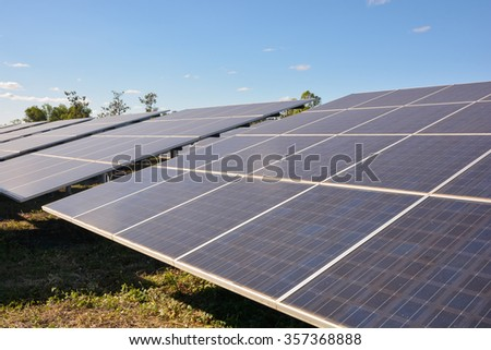 Photovoltaic solar panels on green grass with blue sky