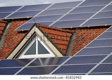 Photovoltaic system on the roof of a house - stock photo