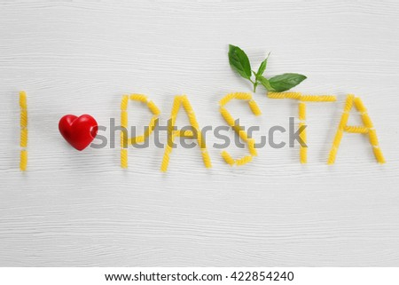 Phrase I LOVE PASTA from fresh uncooked pasta on wooden background - stock photo