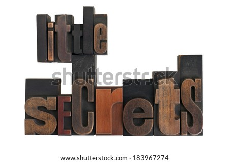 phrase little secrets in vintage wooden letterpress type, scratched and stained, isolated on white background - stock photo