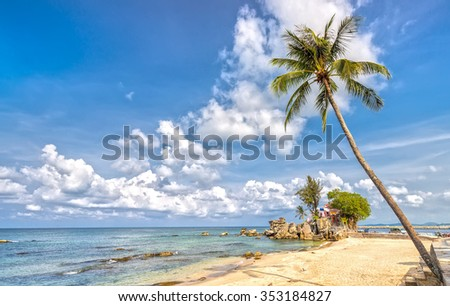 Phu Quoc, Vietnam - April 10th, 2015: Beauty temple on path volcanic rock with coconut trees overlooking island and cloudy blue sky clean beachfront attracts tourists island pearls Phu Quoc, Vietnam