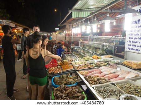 PHU QUOC, VIETNAM - JANUARY 27 2016: A young tourist choose some fresh fish to be cooked on a barbecue in the Duong Dong night market in Phu Quoc island in south Vietnam.