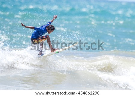 PHUKET - JULY 17: unidentified surfer in action catching waves in rainy season at Kata beach Phuket on July 17, 2016 in Kata beach, Phuket, Thailand.