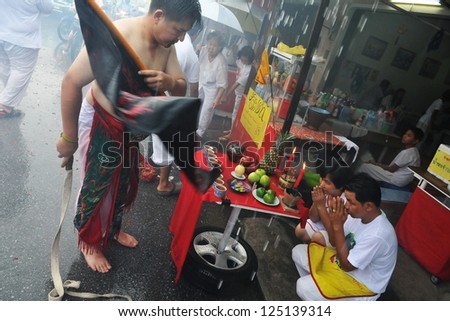 PHUKET - OCT 5: A Taoist devotee blesses a family during a procession to mark the Nine Emperor Festival, known locally as the Phuket Vegetarian Festival, on Oct 5, 2011 in Phuket, Thailand. - stock photo