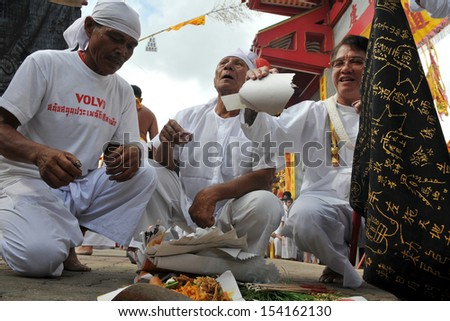 PHUKET - OCT 2: Unidentified Taoist devotees take part in a ceremony of the Phuket Vegetarian Festival on Oct 2, 2011 in Phuket, Thailand. During the festival devotees abstain from eating meat. - stock photo