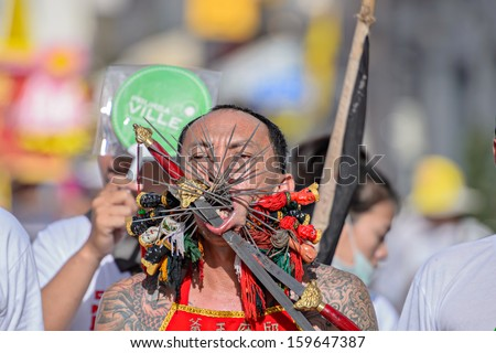 PHUKET - OCTOBER 10: an unidentified Chinese monk possessed by his god walks with his mouth pierced in Phuket Vegetarian Festival October 10, 2013 in Phuket Province, Thailand.