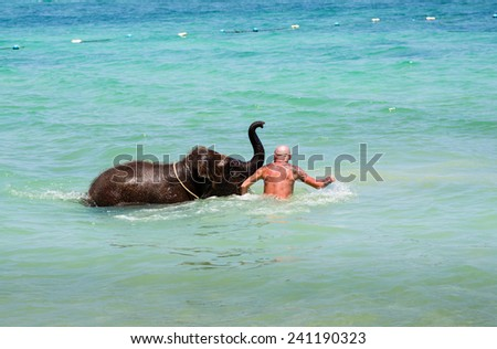Phuket,Thailand - December 19, 2014:  little elephant calf swims in the sea with a man