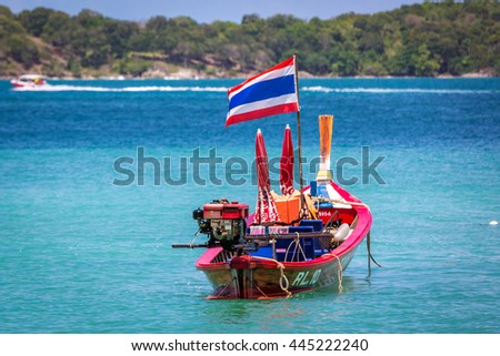 Phuket, Thailand - June 5th 2016 - Traditional boats anchored in a clear blue water shore in Phuket, southern Thailand, Asia.