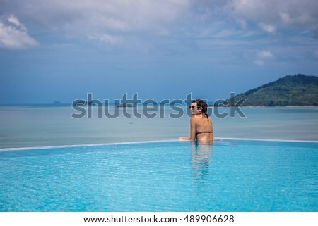 Phuket, Thailand - June 25th.2016 - Young woman enjoying a sunny day around a swimming pool in Thailand, Asia.
